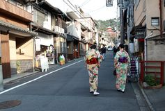 两和服礼服的妇女在对Fushimi Inari寺庙的途中,在京都人将穿全国制服崇拜在寺庙 免版税库存图片