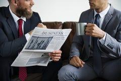 两商人坐有报纸的一个长沙发 免版税库存图片