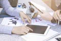 两商人谈论财政图表与片剂和膝上型计算机在室外公园庭院 库存照片