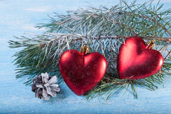 两圣诞节装饰-心脏和杉木锥体积雪的木背景 免版税库存图片
