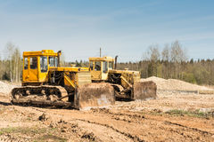 两在一个建造场所的黄色肮脏的老推土机立场在一个晴天反对蓝天背景  免版税图库摄影