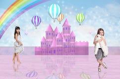 两在一座桃红色神仙的城堡前面的小女孩 免版税库存照片