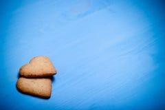 两在一张蓝色木桌上的心形的曲奇饼 定调子 免版税库存图片