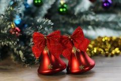 两在圣诞树背景的美丽的红色发光的响铃在木地板上的特写镜头和闪亮金属片 库存图片