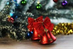 两在圣诞树背景的美丽的红色发光的响铃在木地板上的特写镜头和闪亮金属片 库存照片