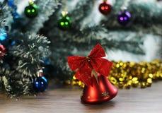 两在圣诞树背景的美丽的红色发光的响铃在木地板上的特写镜头和闪亮金属片 免版税库存照片