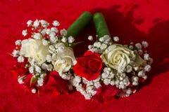 两在天鹅绒红色背景的婚姻的花束 图库摄影