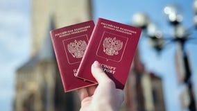 两在女性手特写镜头的红色俄国护照在背景历史的城堡大厦 股票录像