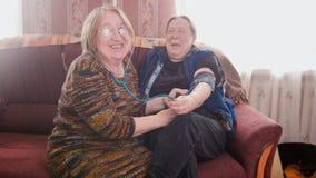 两在家-资深夫人获得乐趣-检查健康状态与测压器-措施压力,领抚恤金者的老妇人 免版税库存图片
