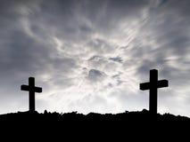 两在小山上面的十字架剪影与在剧烈的天空背景的行动黑暗的暴风云 库存照片