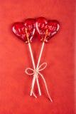 两在心脏形状的棒棒糖在红色背景 库存图片