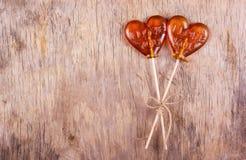 两在心脏形状的棒棒糖在老被佩带的木背景 St华伦泰` s日 免版税库存照片