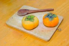 两在斩肉板的柿子和木头匙子 免版税库存图片