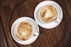 两在木桌上的热奶咖啡咖啡 免版税库存照片