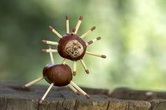 两在树桩,绿色背景的滑稽的栗子动物,传统秋天手工造,狮子 免版税库存图片