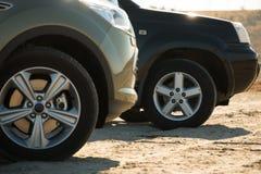 两在沙子停放的SUVs 免版税库存照片