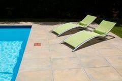 两在游泳池边的空的太阳懒人 库存图片