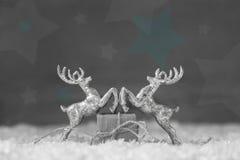 两在灰色破旧的别致的圣诞节backg的银色驯鹿小雕象 免版税库存照片