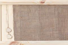 两在用粗麻布报道的木背景,一张卡片的心脏为华伦泰` s天 免版税库存图片