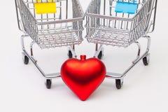 两在白色书桌上和红色听见的购物的台车 免版税图库摄影