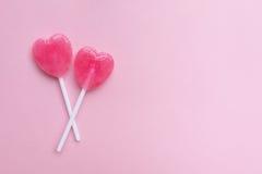 两在空的粉红彩笔纸背景的桃红色华伦泰` s天心脏形状棒棒糖糖果 概念亲吻妇女的爱人 顶视图 库存图片
