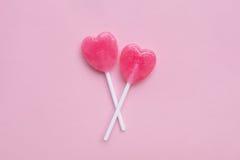 两在空的粉红彩笔纸背景的桃红色华伦泰` s天心脏形状棒棒糖糖果 概念亲吻妇女的爱人 顶视图 免版税库存图片