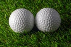 两在草的高尔夫球 免版税库存照片