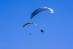 两在蓝天的滑翔伞 库存照片