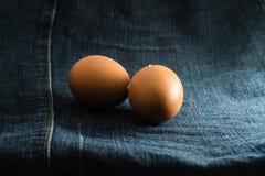 两在蓝色牛仔布的鸡蛋。 免版税库存照片