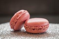 两在闪烁银基地和黑暗的背景的桃红色草莓蛋白杏仁饼干 免版税图库摄影