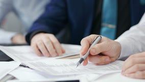 两在队会议显示细节的候宰栏期间的商人的特写镜头手在纸张文件 影视素材