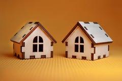 两在黄色背景侧视图的木玩具房子模型 库存图片