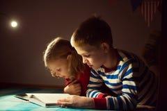 两在黑暗的愉快的兄弟姐妹阅读书与在h的手电 图库摄影