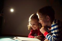 两在黑暗的愉快的兄弟姐妹阅读书与在h的手电 免版税库存图片