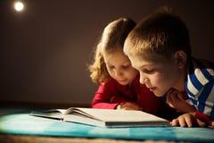 两在黑暗的愉快的兄弟姐妹阅读书与在h的手电 库存图片