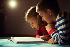 两在黑暗的愉快的兄弟姐妹阅读书与在h的手电 库存照片