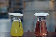两在玻璃水瓶的不同糖浆 免版税库存图片