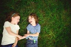 两在绿草的快乐的儿童谎言 库存图片