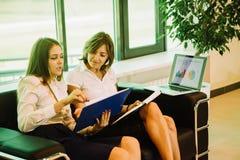 两坐在商业中心的女实业家和谈论想法 免版税图库摄影