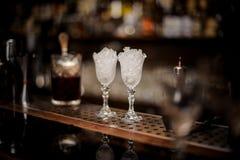 两块典雅的冷却的玻璃用在酒吧柜台安排的冰填装了 免版税库存照片