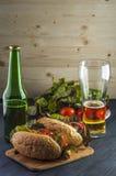 两块可口热狗、啤酒瓶和玻璃在木桌上 库存照片