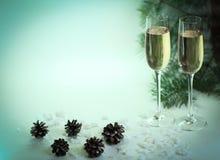 两块在圣诞节背景的玻璃用香槟和锥体 图库摄影