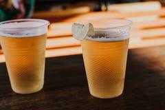 两块塑料玻璃用啤酒肩并肩站立 库存图片