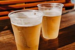 两块塑料玻璃用啤酒肩并肩站立 免版税库存照片