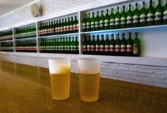 两块塑料玻璃用在瓶背景的啤酒  库存图片
