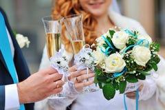两块婚姻的玻璃用香槟在新娘和新郎的手上 免版税库存图片