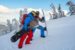 两块愉快的挡雪板在山坡、谈话和lau上升 免版税图库摄影
