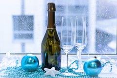 两块玻璃、一个瓶香槟和圣诞节树装饰 免版税库存照片