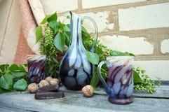 两块玻璃和一个水罐在一个木选项的背景的汁液 库存照片