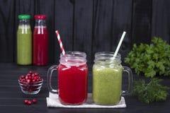 两块玻璃杯子汁液从绿色荷兰芹、莳萝、硬花甘蓝、鲕梨和红色蔓越桔的圆滑的人震动在黑木背景 免版税库存图片